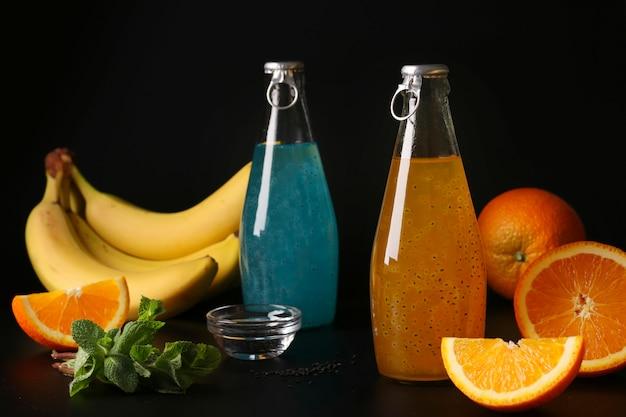 Na moda tropical bebida azul e laranja com sementes de manjericão em garrafa na superfície preta