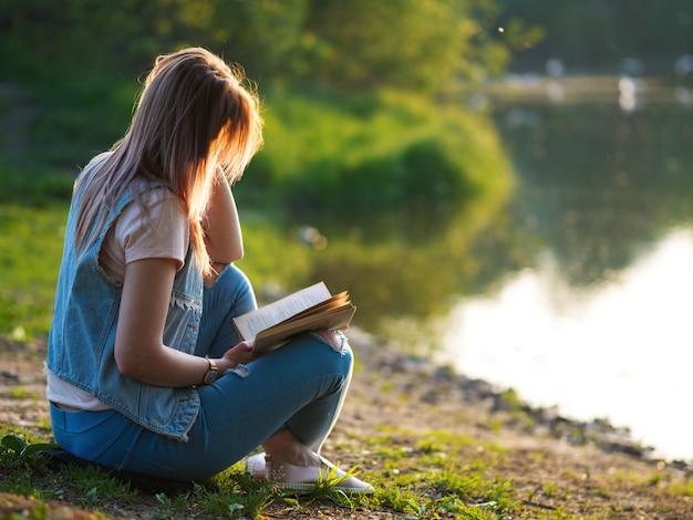 Na natureza, uma bela jovem lendo um livro. pôr do sol de verão à beira do rio no parque