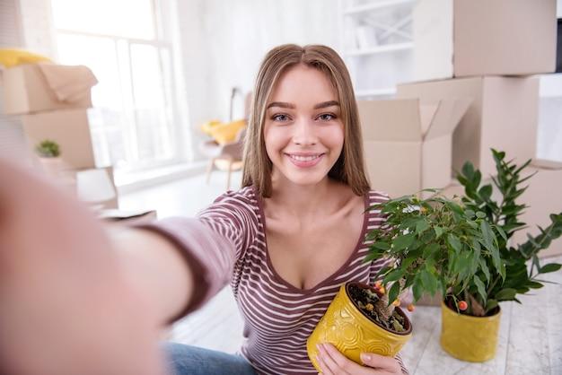 Na nova casa. mulher jovem feliz segurando uma planta e tirando uma selfie enquanto sorri alegremente, tendo se mudado para um novo apartamento