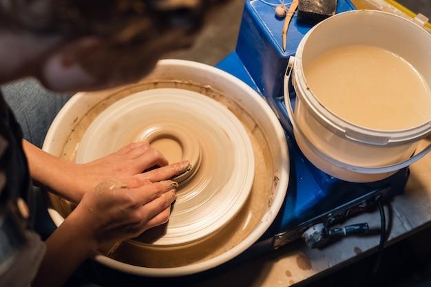 Na oficina, mãos de oleiro esculpem um vaso de argila em uma roda de oleiro.