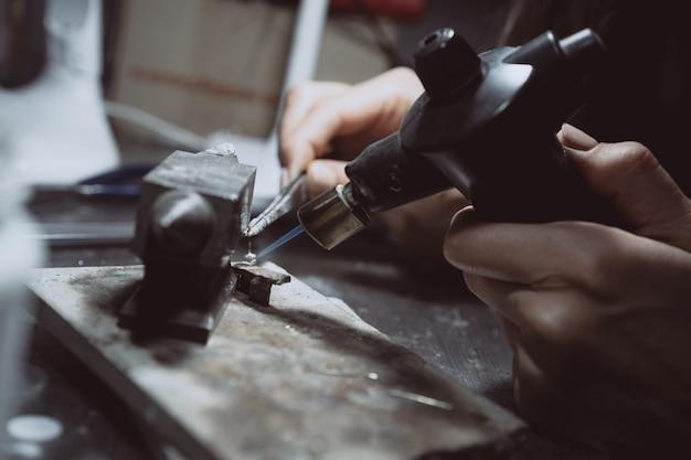 Na oficina, uma joalheira está ocupada soldando joias