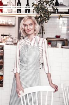 Na padaria. linda mulher loira em pé perto da cadeira enquanto trabalhava na padaria