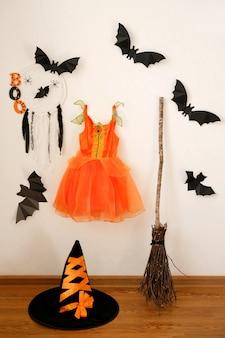 Na parede da sala está pendurado um vestido laranja de bruxa para uma festa de máscaras de halloween