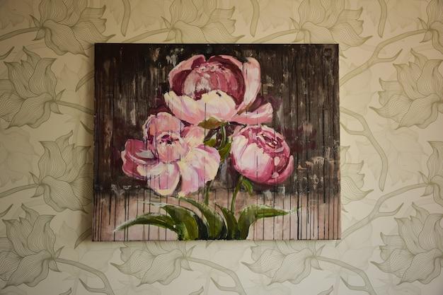 Na parede decorada, no meio da moldura, há um quadro com flores pintadas