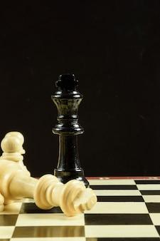 Na peça do tabuleiro de xadrez está uma figura do rei, atrás da figura está um fundo preto.
