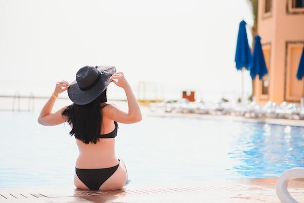 Na praia da piscina. pessoas, mulher, estilo de vida, relaxe e descanse perto de piscinas luxuosas, tome sol em casa
