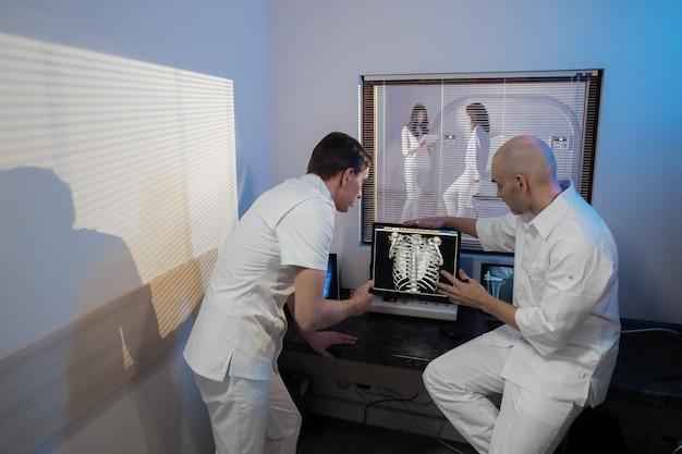 Na sala de controle, médico e radiologista discutem diagnóstico enquanto assistem ao procedimento