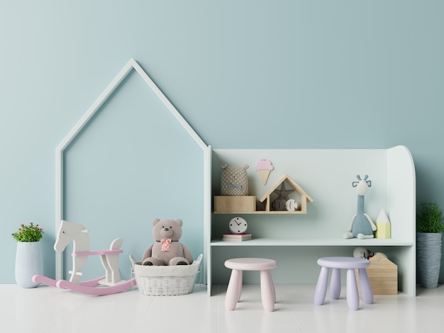 Na sala de jogos infantil com tenda e mesa sentado boneca na parede azul vazia.