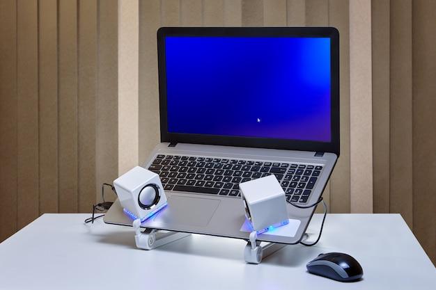 Na superfície da mesa está um laptop com tela azul montada em suporte de refrigeração e dois alto-falantes usb brancos com luz de fundo azul e mouse de computador.