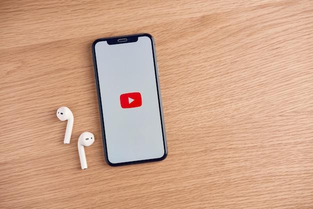 Na tela do youtube na apple iphone em cima da mesa, o youtube é o popular site de compartilhamento de vídeos online.