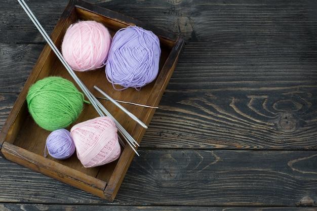 Na velha caixa de madeira artigos para tricô: agulhas de tricô, ganchos, bolas de fio
