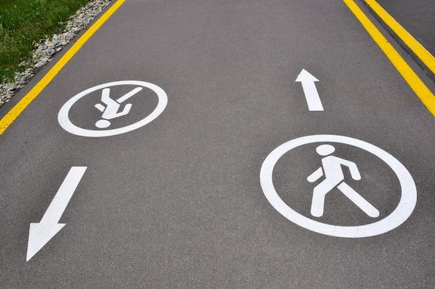 Na via de asfalto há sinalização para pedestres nos dois sentidos, permitindo trânsito para caminhada na calçada