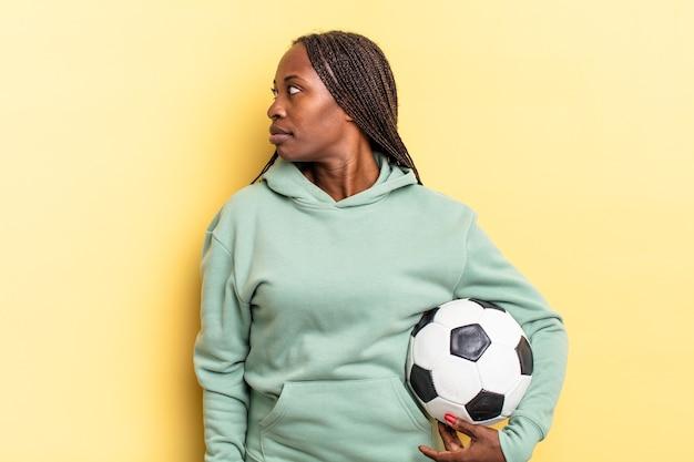Na vista de perfil olhando para copiar o espaço à frente, pensando, imaginando ou sonhando acordado. conceito de futebol