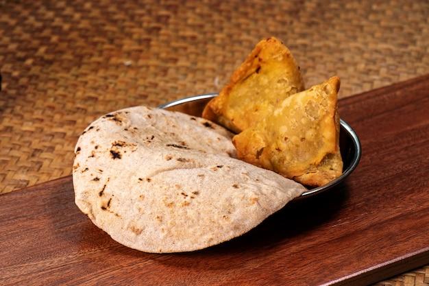 Naan pão e samosa para caril indiano no prato na mesa de madeira, cozinha tradicional indiana