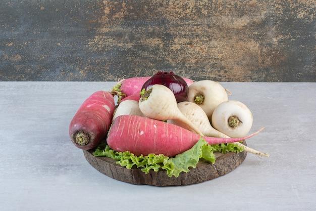 Nabos brancos e vermelhos com cebola na peça de madeira. foto de alta qualidade