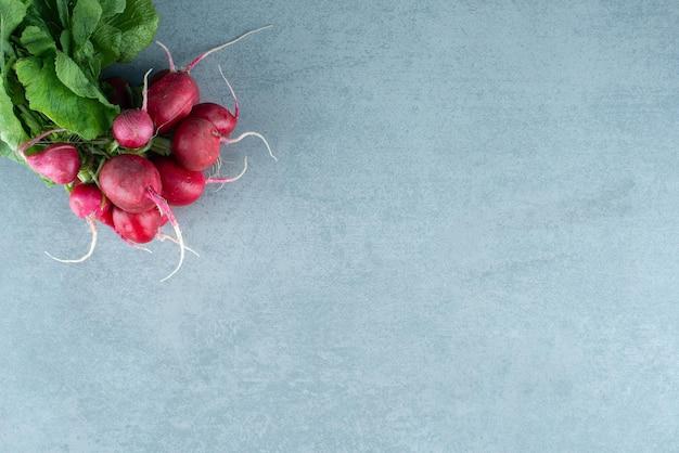 Nabos vermelhos frescos no mármore.