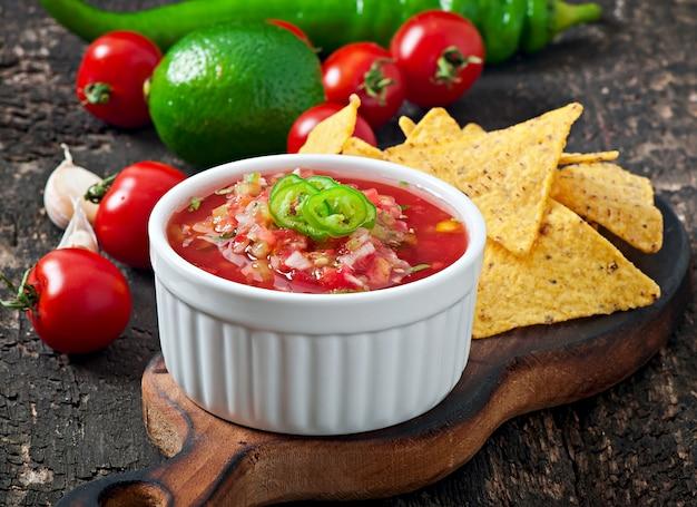 Nacho mexicano chips e molho de salsa em tigela sobre fundo de madeira