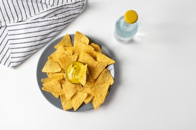 Nachos chips de milho com molho de queijo na vista de cima da mesa branca, garrafa de refrigerante, guardanapo listrado