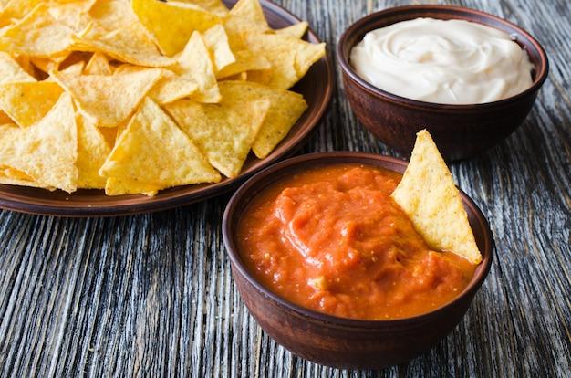 Nachos chips de milho com tomate picante e molhos de queijo.