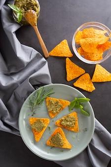 Nachos chips ou chips mexicanos de milho com lanche de comida saudável de massas pesto, vista superior