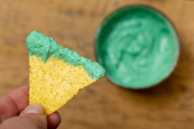 Nachos com molho verde orgânico na mão