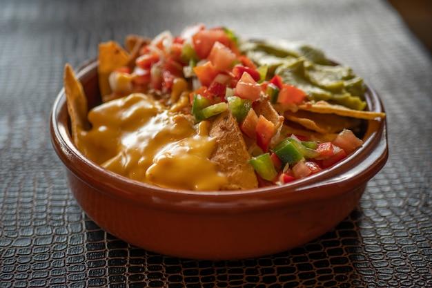 Nachos com queijo cheddar e guacamole em uma panela de barro sobre uma mesa escura
