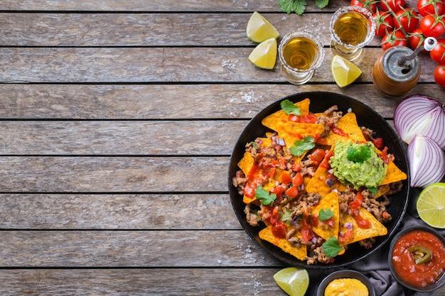 Nachos de tortilla de milho amarelo com carne moída, carne moída, guacamole, molho de pimenta jalapeño e molho de queijo com tequila em uma mesa de madeira. vista superior do plano de fundo do espaço da cópia