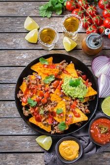 Nachos de tortilla de milho amarelo com carne moída, carne moída, guacamole, molho de pimenta jalapeño e molho de queijo com tequila em uma mesa de madeira. vista superior do plano de fundo
