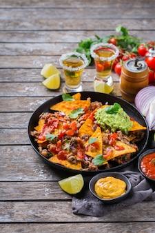 Nachos de tortilla de milho amarelo com carne moída, carne moída, guacamole, molho de pimenta jalapeño e molho de queijo com tequila em uma mesa de madeira.