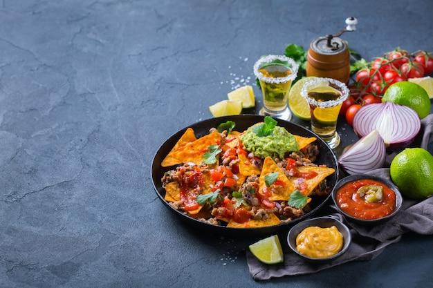 Nachos de tortilla de milho amarelo com carne moída, picadinho, guacamole, molho de pimenta jalapeño e molho de queijo com tequila em uma mesa escura. copie o fundo do espaço