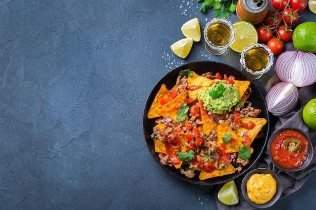 Nachos de tortilla de milho amarelo com carne moída, picadinho, guacamole, molho de pimenta jalapeño e molho de queijo com tequila em uma mesa escura. vista superior do plano de fundo do espaço da cópia