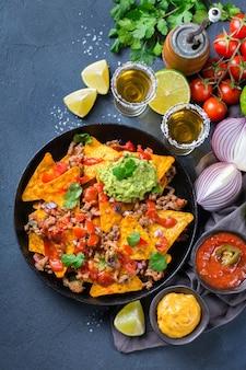 Nachos de tortilla de milho amarelo com carne moída, picadinho, guacamole, molho de pimenta jalapeño e molho de queijo com tequila em uma mesa escura. vista superior do plano de fundo