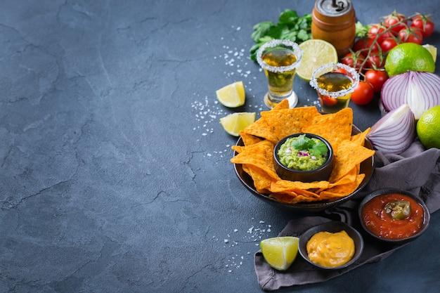 Nachos de tortilla de milho amarelo com guacamole, molho de pimenta jalapeño e molho de queijo com tequila em uma mesa escura. copie o fundo do espaço
