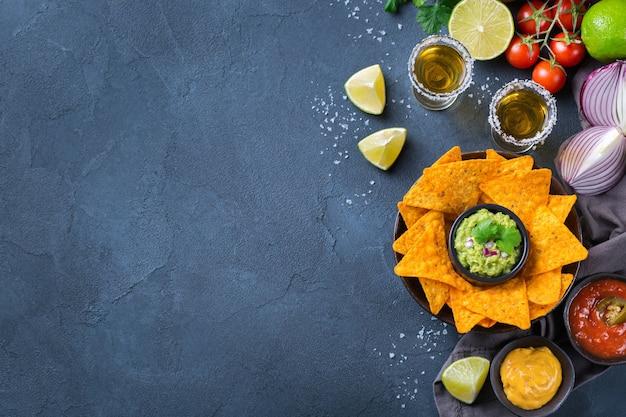 Nachos de tortilla de milho amarelo com guacamole, molho de pimenta jalapeño e molho de queijo com tequila em uma mesa escura. vista superior do plano de fundo do espaço da cópia
