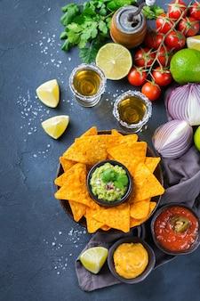 Nachos de tortilla de milho amarelo com guacamole, molho de pimenta jalapeño e molho de queijo com tequila em uma mesa escura. vista superior do plano de fundo