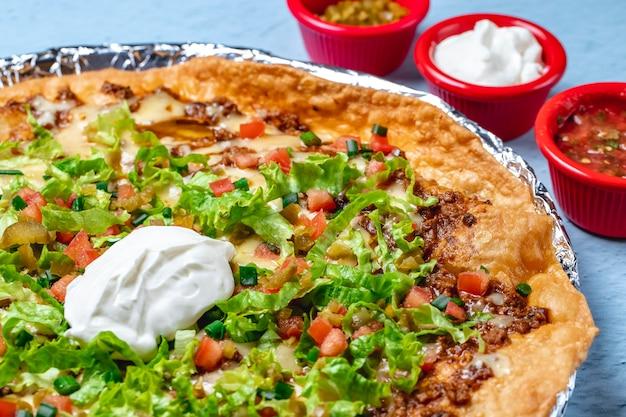 Nachos de vista lateral tortila frita com carne moída queijo alface de tomate fresco cebolinha creme de leite e pimenta jalapeno picada e molhos em cima da mesa
