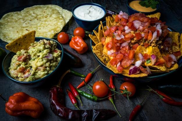 Nachos e queijo chedar com guacamole de pimentão sour cream e tortilla pico de gallo