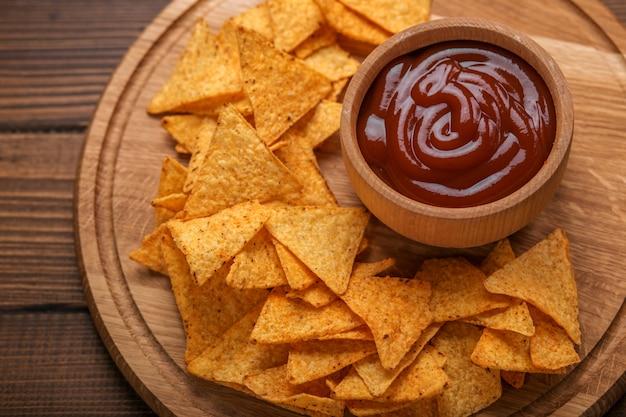 Nachos mexicanos chips com molho de tomate picante em fundo de madeira