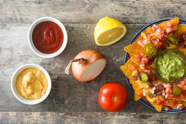 Nachos mexicanos com carne, guacamole, molho de queijo, pimentão, tomate e cebola no prato na mesa de madeira