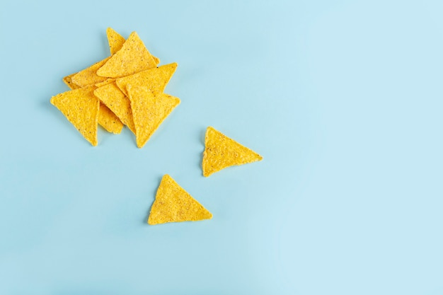 Nachos mexicanos tradicionais, chips de tortilha de milho sobre fundo azul.