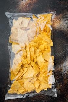 Nachos, pacote triangular de aperitivo de milho mexicano tradicional, em mesa rústica escura velha, vista de cima ou lay-out