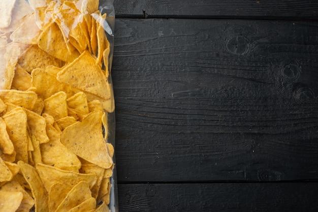 Nachos, pacote triangular de aperitivo mexicano de milho tradicional, em mesa de madeira preta, vista de cima ou lay-out