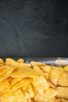 Nachos, pacote triangular de aperitivos de milho mexicano tradicional, em mesa preta, vista de cima ou lay-out