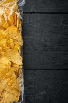 Nachos, tortilha de milho em saco, em mesa de madeira preta, vista de cima ou de cama