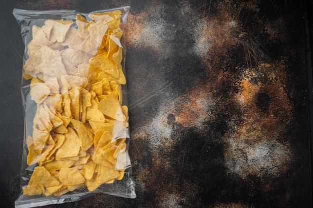 Nachos, tortilla de milho em saco, em uma velha mesa escura rústica, vista de cima ou plano plano