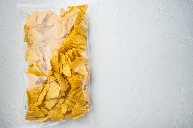 Nachos, tortilla de milho em saco, na mesa branca, vista de cima ou plano