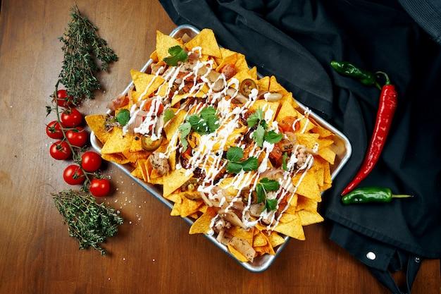 Nachos - um aperitivo mexicano clássico feito com tortilhas de milho. nachos com molhos e holopenya. vista do topo. fechar-se.