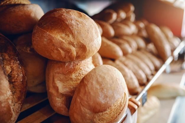 Naco de pão delicioso fresco na fileira nas prateleiras prontas para a venda. interior da padaria.