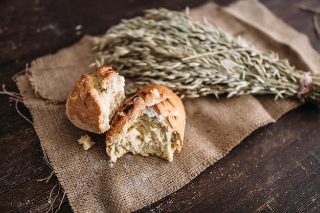 Naco de pão fresco com crosta crocante partida ao meio e cacho de trigo em pano de estopa. conceito de padaria caseira, comida orgânica natural.