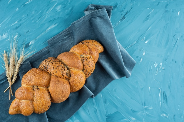 Naco de pão trançado recém-assado sobre uma toalha de mesa escura.